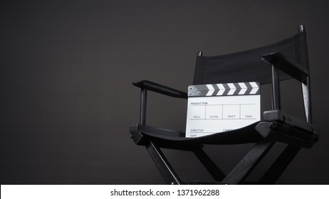 Clapperboard or clap board or movie slate with black director chair use in video production ,film, cinema industry on black background.