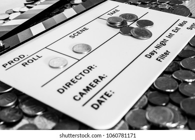 Clapperboard with coins above and on it creating a relation between filmmaking and business (Black and White version)