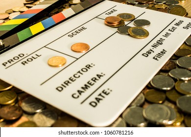 Clapperboard with coins above and on it creating a relation between filmmaking and business