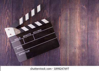 a Clapperboard lies on a wooden background