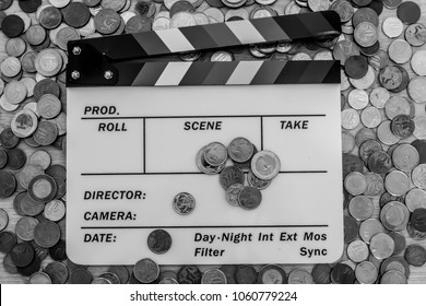 Clapperboard with many coins surrounding, above and on top of it (Black and White version)