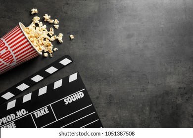 Clapperboard and popcorn on table