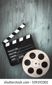 Clapperboards and the reel of film lie on a wooden board.