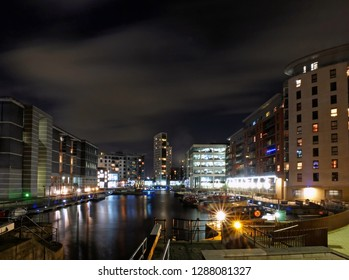 Clarence dock leeds at night with moored barges and moonlit clouds over brightly illuminated waterside buildings reflected in the harbour