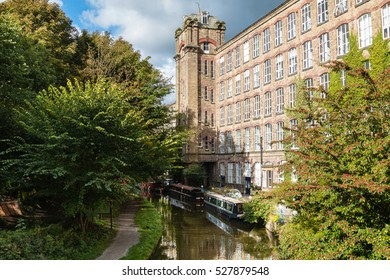 Clarence Mill - an old silk mill - on the banks of the Macclesfield Canal in Bollington Cheshire with moored narrow boats.