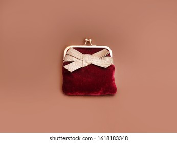 Claret red velvet purse with gold ribbon as women's fashion accessories, flat lay on brown background