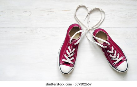 Claret sneakers with heart on wooden white floor background. Concept of Love.