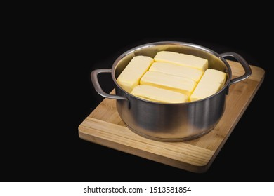 Clarification of butter, butter cubes in a steel pot on a chopping board and black isolated background.