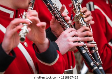 Clarinet musicians in red uniform playing playing music on their instruments