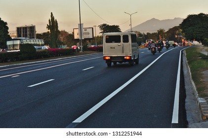 Clark Pampanga, Philippines - January 25, 2019: Main road in Clark with some vehicles and a small portion of Mount Pinatubo in the Background.
