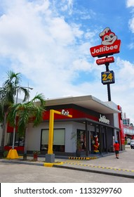 Clark, PH - JULY 2, 2018: The drive-thru Jollibee restaurant, the most popular fried chicken and fast foods franchise in Philippines, showing on highway with cloudy blue sky background.