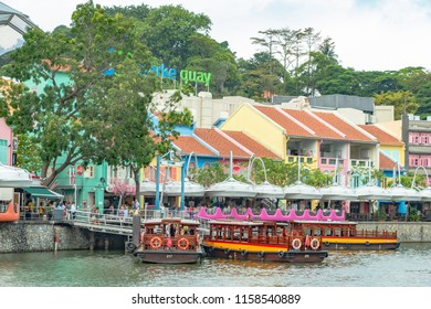 Clarke Quay, Singapore - Mar 4, 2018: River cruise services along banks of the Singapore river, vintage parking bumboats on historic waterway become the icon of this river to visitors and locals