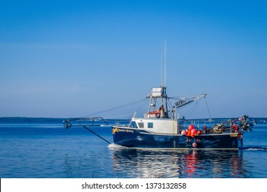 Clarks Harbour, Nova Scotia, Canada, March 27 2019; Lobster fishing boats arrive to home port wharf after a long day of pulling traps and gear.