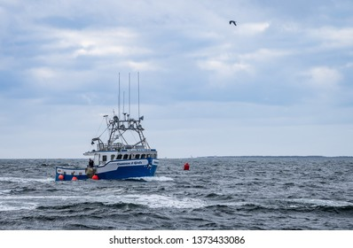 Clarks Harbour, Nova Scotia, Canada, April 02 2019; Lobster fishing boats arrive to home port wharf after a long day of pulling traps and gear.