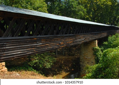 Clarkson Covered Bridge, in Cullman, Alabama, is wooden and extremely long and crosses Crooked Creek.  Tin roof covers bridge.