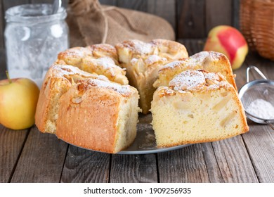 Clasic sponge cake with apples on wood table, selective focus. Homemade cake