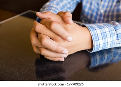Clasped hands resting on dark reflective table top, blue plaid shirt sleeves.