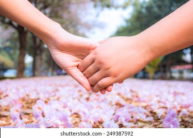 Clasping hand on pink flower background