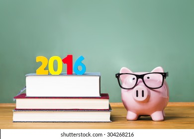 Class of 2016 theme with textbooks and piggy bank with glasses on green chalkboard background
