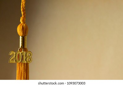 Class of 2018. Gold tassel drop graduation gown accessory and keepsake charm with side lighting. Iconic symbol of a graduate's academic and life success.