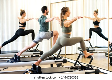 Class in a gym doing pilates standing lunges on reformer beds to stretch and tone the muscles reflected in a wall mirror
