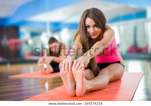 Class and instructor doing stretching pilate exercises in fitness studio