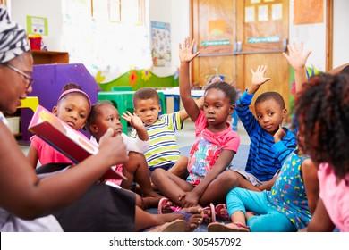 Class of preschool children raising hands to answer teacher
