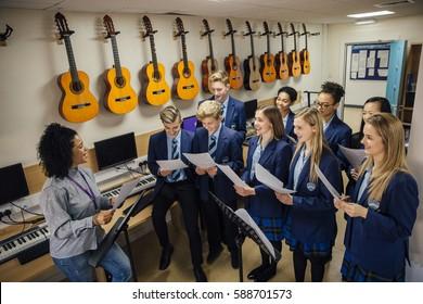 Class of teens are in their music lesson at school. There is a female teacher and the class are practicing choir with her.