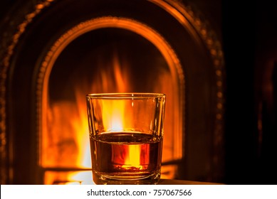 A class of whiskey by a cosy fireside.