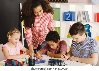 Class working with teacher during lesson in school