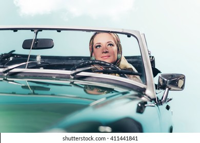 Classic 1960s fashion woman with headscarf driving sports car.