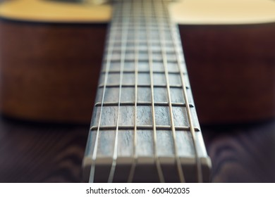 Classic acoustic guitar at weird and unusual perspective closeup. Coloring photo with soft focus. Musical instruments shop or learning school concept.