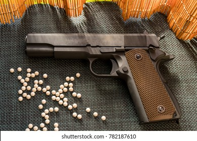 Classic airsoft guns produced since World War II. Have a BB ball on the side. Placed on a dark mat. The back is a bamboo light natural scene.