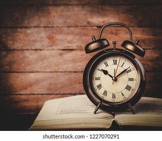 classic alarm clock with bell on a book on wooden table.