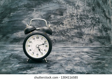 Classic alarm clock on vintage dark background, time is running out concept