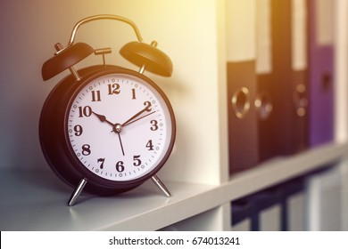 Classic alarm clock showing time during working hours or work break in business office, selective focus