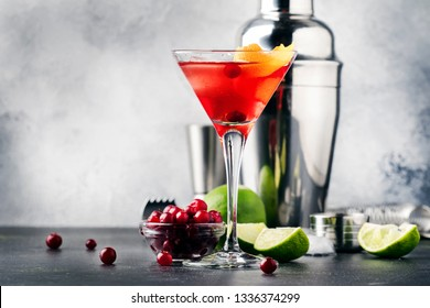 Classic alcoholic cocktail cosmopolitan with vodka, liqueur, cranberry juice, lime, ice and orange zest, gray bar counter background, bartender tools, space for text
