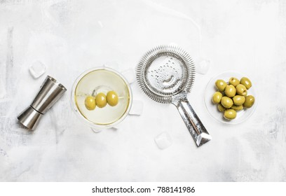 Classic alcoholic cocktail with dry vermouth and green olives, bar tools, gray background, top view