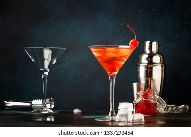 Classic alcoholic cocktail Manhattan with bourbon, red vemuth, bitter, ice and cocktail cherry in glass, night bar background, place for text, selective focus