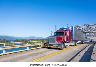 Classic American big rig burgundy semi truck with refrigerated semi trailer with reefer unit on it driving on truss Bridge of God with view of Columbia River Gorge area for timely goods delivery