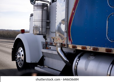 Classic American Big Rig Semi Tractor with custom chrome accents and parts for reach looking drive with cargo on interstate highway with reflection of surraunded trees and sky