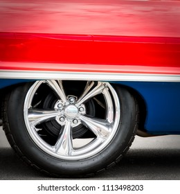 A classic American car, with updated hubcaps, from the sixties in red, white, and blue.