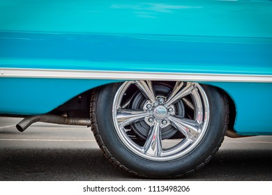 A classic American car, with updated hubcaps, from the sixties in baby blue.
