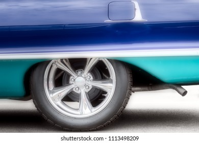 A classic American car, with updated hubcaps, from the sixties in two tone blue.