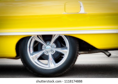 A classic American car, with updated hubcaps, from the sixties in yellow.