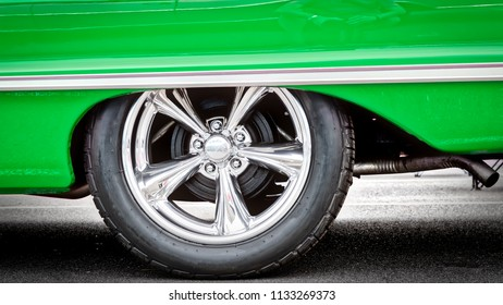 A classic American car, with updated hubcaps, from the sixties in green.
