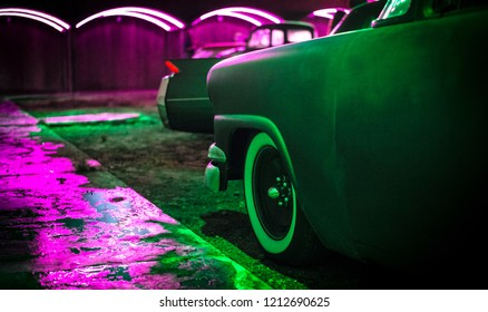 Classic American cars are bathed in colorful neon lights.