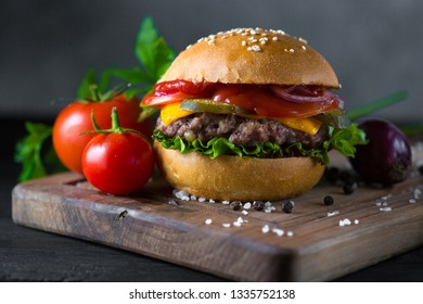 Classic american cheeseburger on a wooden board with tomatoes and onion
