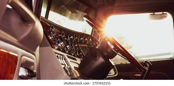 Classic american commercial semi truck with stylish chrome gauges panel and custom luxury wooden steering wheel. Luxurious and comfortable cabin of 18 wheeler truck at evening, back lit, warm filter.