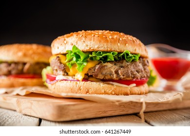 Classic american hamburger with beef and tomato sauce on dark background.